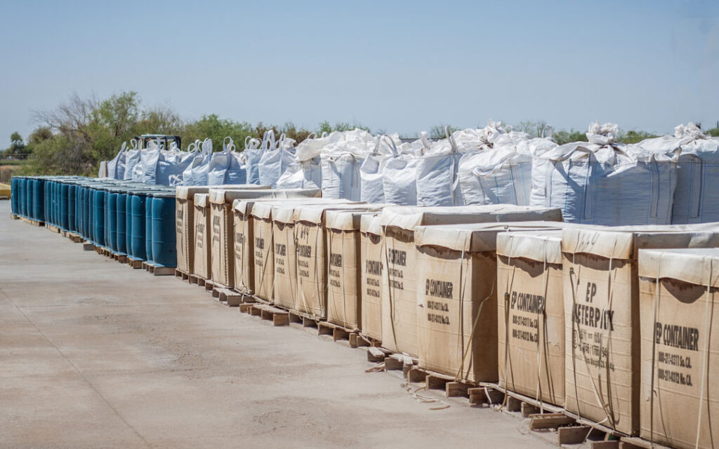Lengthy pile of metal recyclables in boxes and bags